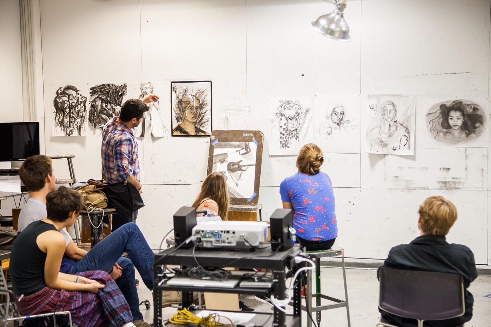 Fine arts class with faculty and students looking over drawings