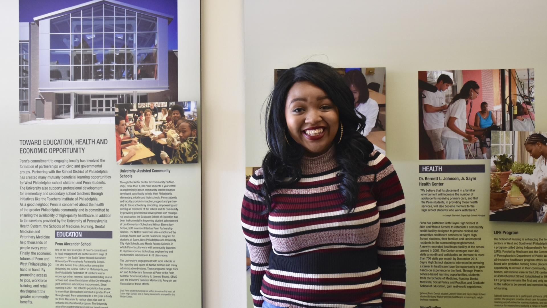 Student in front of signs in the Netter Center for Community Partnerships