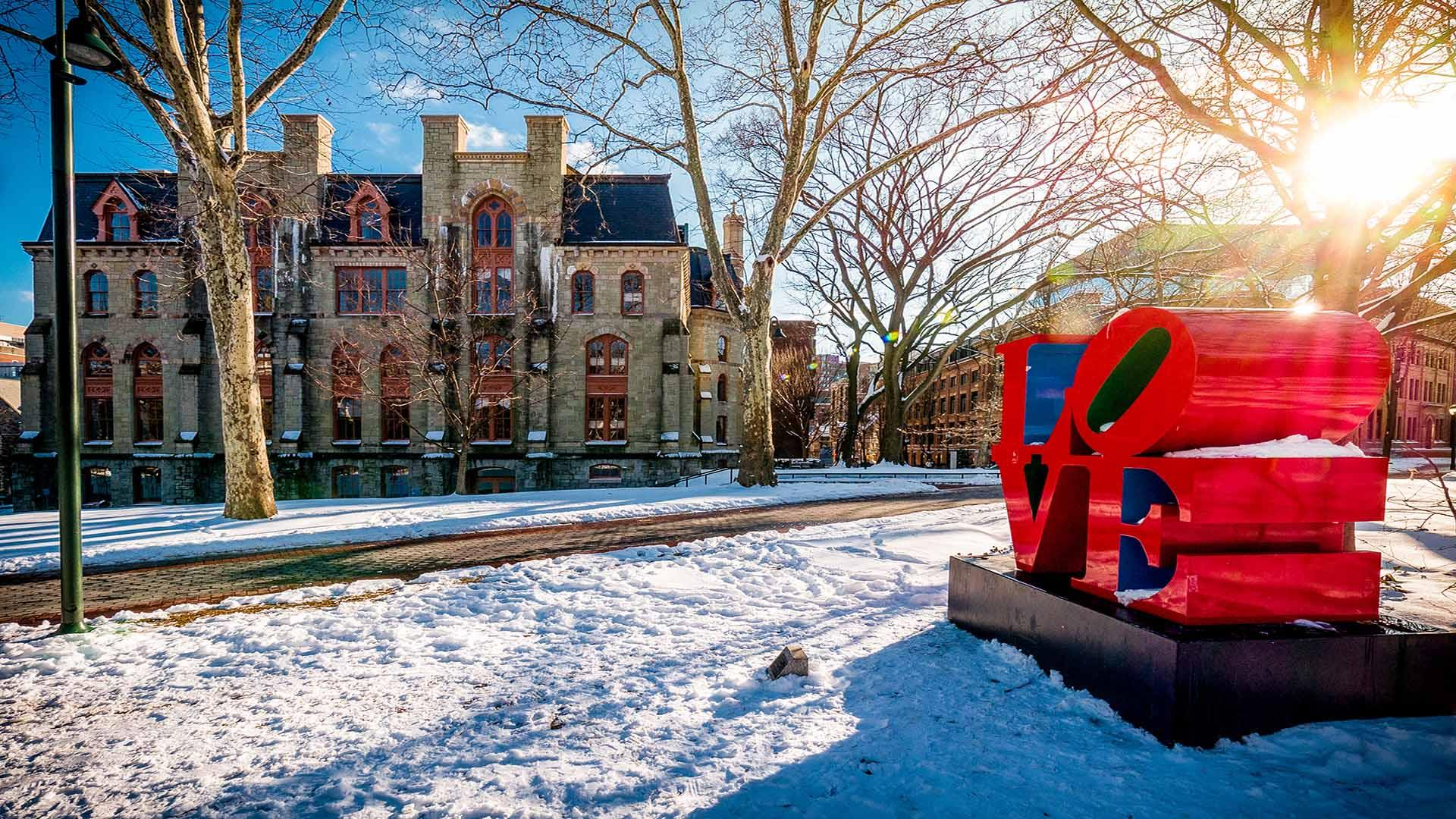 Winter photo with snow, Claudia Cohen Hall, and Love Statue on Penn's campus