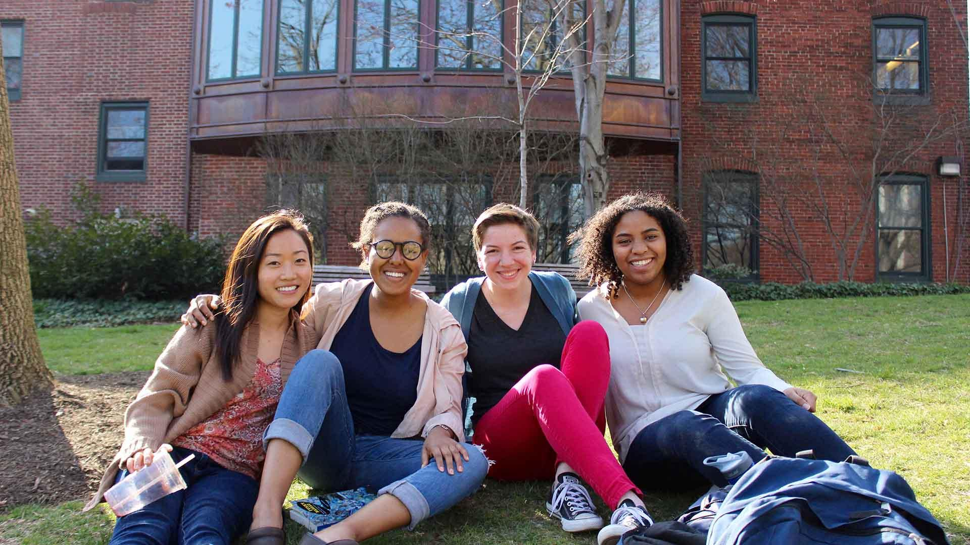 Students sitting on the grass outside Sweeten Alumni House