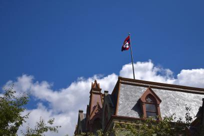 Roof of College Hall featuring the Penn flag