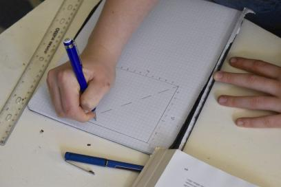 Student hands drawing a line graph