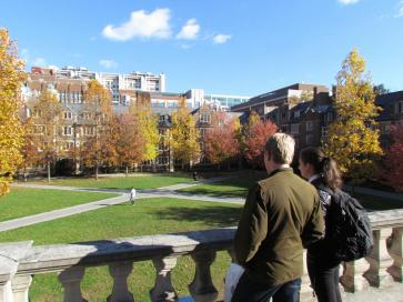 Two students overlooking the Quad dormitory in fall